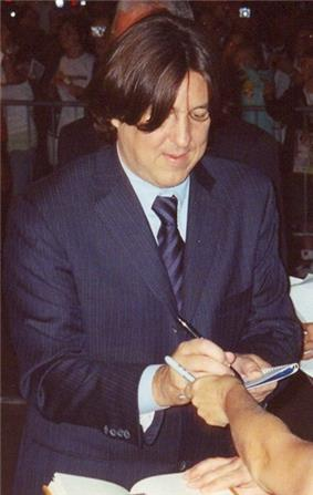 A man wearing a suit looks down at the peace of paper he is signing for the person who is out of shot.