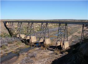 A small stream in arid country flows under a railroad bridge high above the water.
