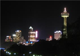 A spike tower with a pod is lit along its length on the right. Other buildings show interior lights in this night scene. The foreground is a deep black sky.