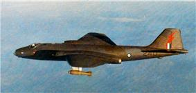 A two engined jet aircraft in mid-flight, a single bomb is evident on an underwing pylon.
