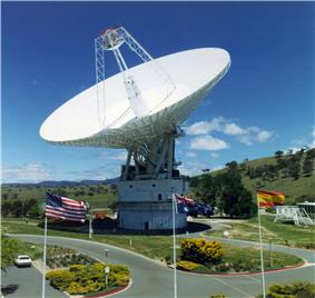 White satellite dish pointed upwards with United States, Australian, and Spanish flags in foreground