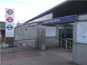 A grey building with a black top and a blue sign reading