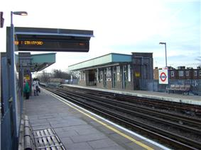 A railway platform with a railway track running through it from the left portion of the background to the right portion of the foreground