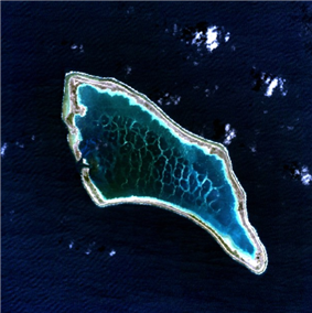 aerial view of a small atoll surrounded by deep blue ocean, a narrow strip of land around a wide area of dappled water in its roughly oblong shaped lagoon.