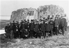 A group of men standing in front of Parry's wintering rock in 1909