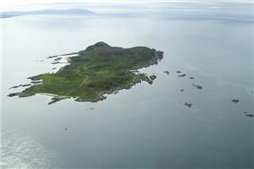 A green island sits in a clam sea. There are numerous small islets in the surrounding waters.