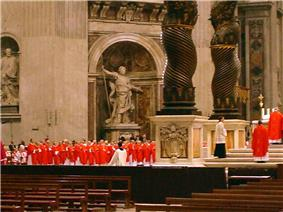 The cardinals, all in bright red robes, are grouped near the baldachin.