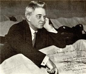 photograph of Carl Nielsen in a dark suit and tie sitting behind crumpled papers including a letter with his signature