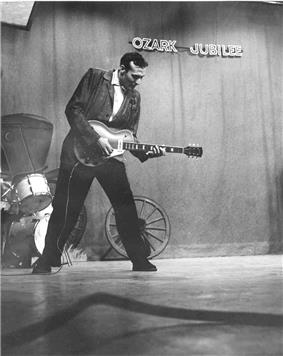 Carl Perkins plays guitar on stage