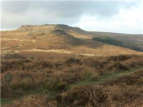Photograph showing a moorland view. The moor is covered in heather of varying shades of brown. Stones are scattered across the moor. In the middle distance there is a rock outcrop atop a small hill. Behind it is a larger hill with a flat top.