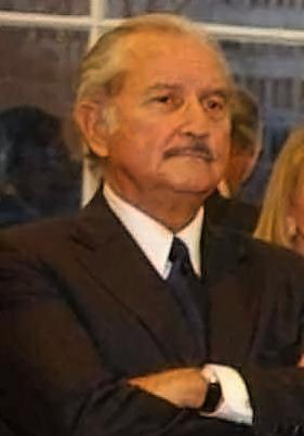 Head and shoulders photo of a greying man with a small moustache, wearing a suit, arms folded.
