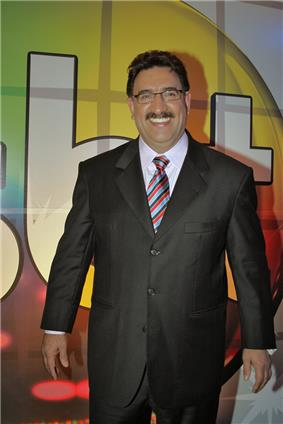 Smiling, middleaged, darkhaired mustachioed man, wearing glasses and a suit