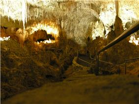 A picture of a partially illuminated underground cave with a jagged rock ceiling and a walkway extended into the cavern.