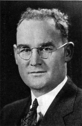 Quarter-length black-and-white image of a man. He is wearing a jacket and tie, and his hair is short. He is wearing spectacles