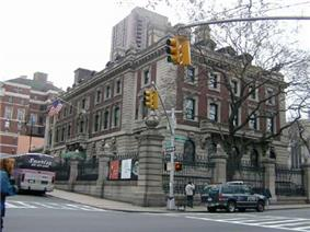 A three story brick and stone building sits on a corner in New York City and is surrounded by a stone and wrought iron fence.
