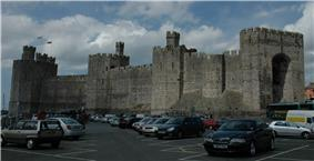 A medieval-style castle with a parking lot in the foreground.
