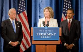 A pale-skinned man in his sixties with white hair, a pale-skinned woman in her fifties with light brown hair, and a brown-skinned man in his forties with dark hair, all stand in front of a blue drape backdrop with two American flags. Both men are wearing dark business suits with white shirts and ties, one blue, one red; the woman is wearing a light beige suit jacket. The woman is behind a brown podium with a blue and white sign saying