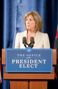 A pale-skinned woman in her fifties with straight, light brown hair parted near the middle and falling to above the shoulders, wearing a light beige suit jacket, listening with a serious expression to an unseen question as she stands behind a brown podium with a blue and white sign saying