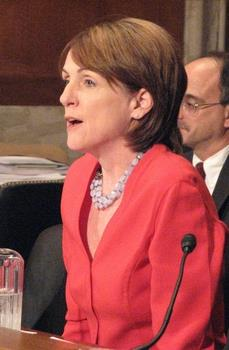 A pale-skinned woman in her early fifties is sitting behind a brown table, speaking, with a microphone and a pitcher of water. She has brown hair around the ear down to her shoulder, and is wearing a salmon-colored suit jacket with a double-strand of some kind of necklace. A balding, middle-aged man and a stack of some papers can be seen behind her.