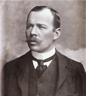 Head and shoulders portrait of a man with receding hair, heavy moustache, looking left from the image. He wears a high white collar, black necktie, dark waistcoat and jacket.