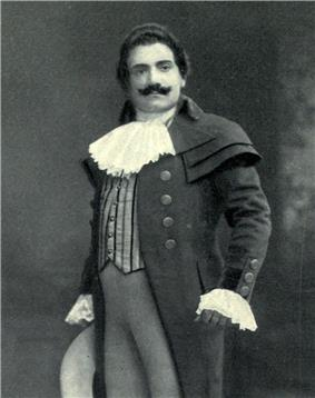 Man, with dark hair and a curling moustache, standing in a posed position. He is wearing a long coat, with lace at the throat and cuffs.