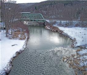 A view of a creek with a truss bridge in the near background and another bridge in the far background.