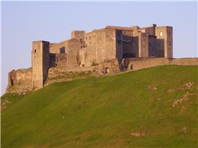 Castle against sky, with sloping grass in front