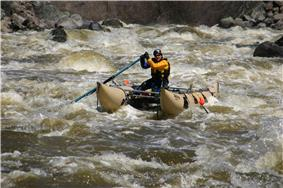 A man on a cataraft paddling through rapids of foam and green water