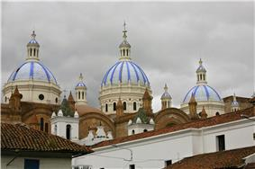 Roofs and towers of a small white church and a larger brown brick church with three large white-blue cuppolas.