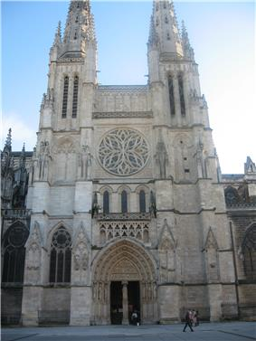 A cathedral in white stone. The west façade has a single entrance with a monumental rose window above it. The entrance and rose window are flanked on each side by a gothic bell tower and spire.