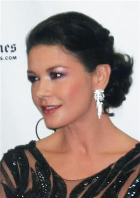 A photo of a black haired woman wearing earrings and a black dress.