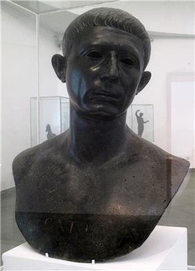 A bronze bust of the head and shoulders of a middle-aged man, with the word