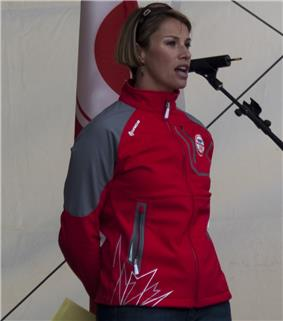 A woman with short blonde hair speaks into a microphone to an unseen audience. She is wearing a red and grey coat.