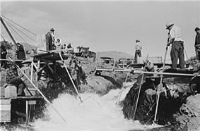 Four men dressed in long-sleeved shirts, long pants, and hats are perched on platforms on both sides of a rushing stream. Three of the men are standing, and one is seated. Each man holds one end of a long pole with a net, dipped in the water, attached to the other end. Several people without poles are watching or waiting nearby.