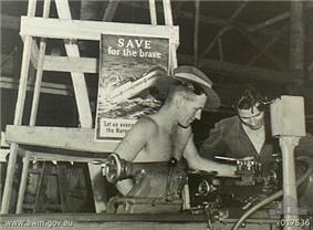Black-and-white photograph of two soldiers working with a lathe. A poster behind them depicts a ship with hospital markings sinking by the bow and is captioned with