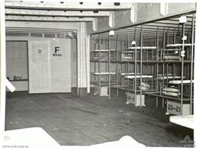 Inside of a medical ward aboard a ship: Bunk beds line the right side, other furnishings protrude into the bottom edge of the photograph, but apart from these, the room is empty. A door at the far end of the room has the text
