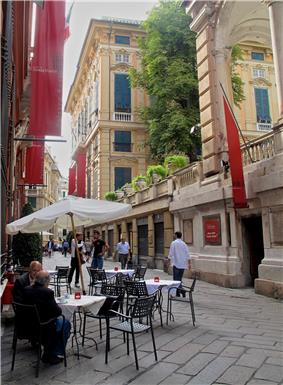 Narrow street lined by four storied buildings.