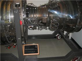 An engine public show at national museum, with the front aft facing left. Sections of the casing are trimmed out and replaced with clear plastic revealing booster vane, compressor and turbine blades, from left to right.