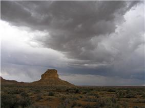 Dark, rolling storm clouds lower over a desert landscape; a butte stands in the near distance, left of center.