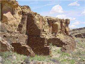 Cliff-side set of ruined walls in daytime. In front of a cliff running diagonally from near left to middle right, rectangular slabs of stone, each somewhat smaller than a common brick, are stacked to compose a wall. Walls are seen delimiting several smallish rectangular