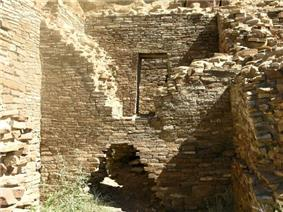 Inside daytime view of a ruined and ceiling-less rectangular room. Tawny-beige stacked sandstone bricks compose walls rising from brush-covered ground. The several walls visible in the image are up to perhaps a dozen feet in height. In the wall immediately at center, a triangle-shaped entrance several feet high leads to an adjacent chamber behind. The upper part of the same wall, shaped like an inverted-triangle, has fallen away or otherwise been removed, revealing a rectangular doorway leading to yet another concealed room. At left and right are two similar walls perpendicular to the one at middle.