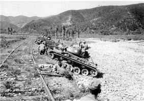 A line of soldiers and tanks hides beneath a berm