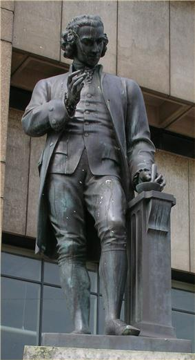 Statue of a man with a mortar and pestle in his left hand and his right hand upraised