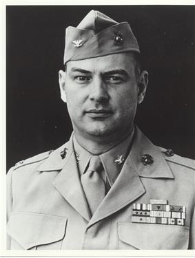 Head and shoulders of a middle-aged white man with a round face wearing a garrison cap and a jacket with four rows of ribbon bars on the left breast and pins on both the lapels and on the collar of the undershirt.