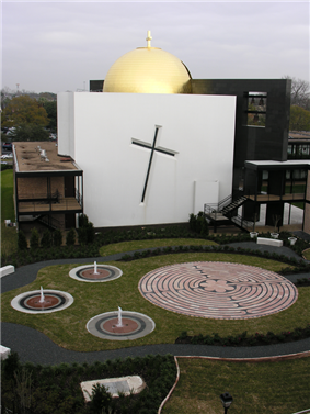 Concrete facade of the building is adorned only with a cross, etched at an angle, and a gold dome on top. Visible are external stairs, halls and lobbies. In the back is a standalone wall that bisects the dome, in which there is a window with bells.