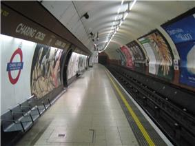 The interior of a building with a rounded ceiling and walls, three benches on the left, a railway track on the right, and advertisements on the walls