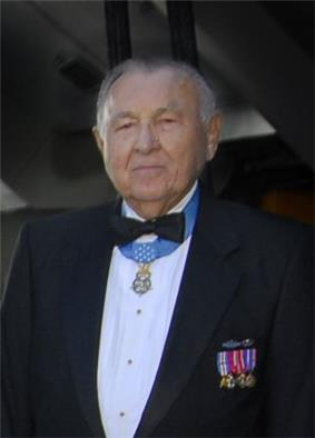 Head and shoulders of an elderly white man with a round face, wearing a tuxedo with military medals pinned to the chest and one medal hanging from a light blue ribbon around his neck.
