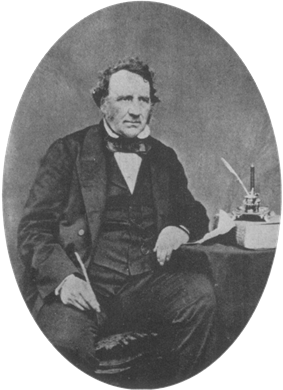 A middle aged Victorian gentleman sits beside a table wearing a dark suit with waistcoat and bow tie. His left elbow rests on the table. In his right hand he holds a quill pen.