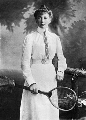 A black and white picture, a woman is in all-white attire with a tie on, and is looking right at the camera in the photograph with a racket in her right hand