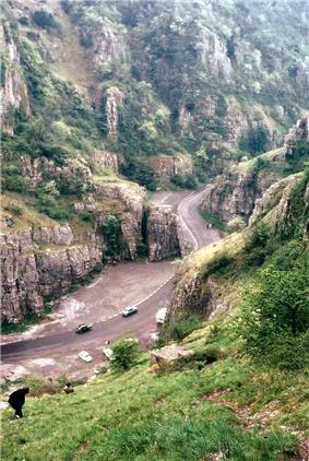 Exposed limestone cliffs on either side of a road with cars on it.